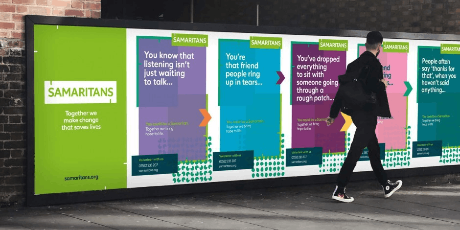 man walks past advertisement of Samaritans